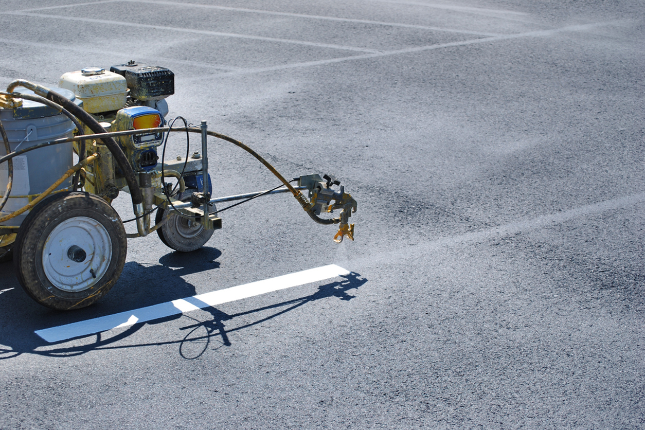 Striping machine painting lines onto fresh asphalt.