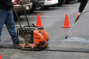 Asphalt patch repair. This image shows a tamper/vibrating machine compressing a new asphalt patch.