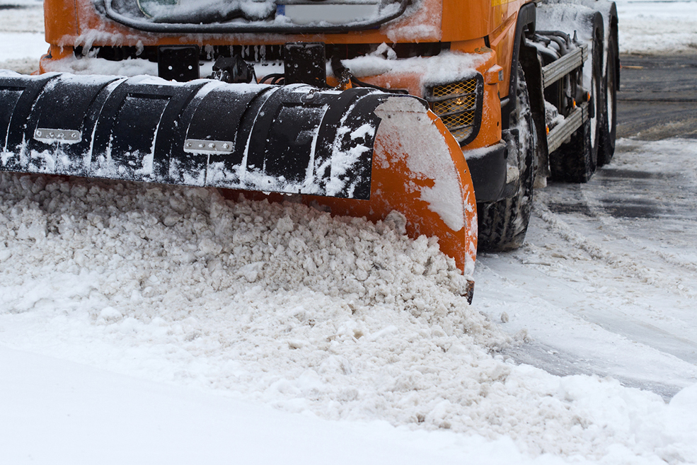 front view of an orange snow plug working on a city street
