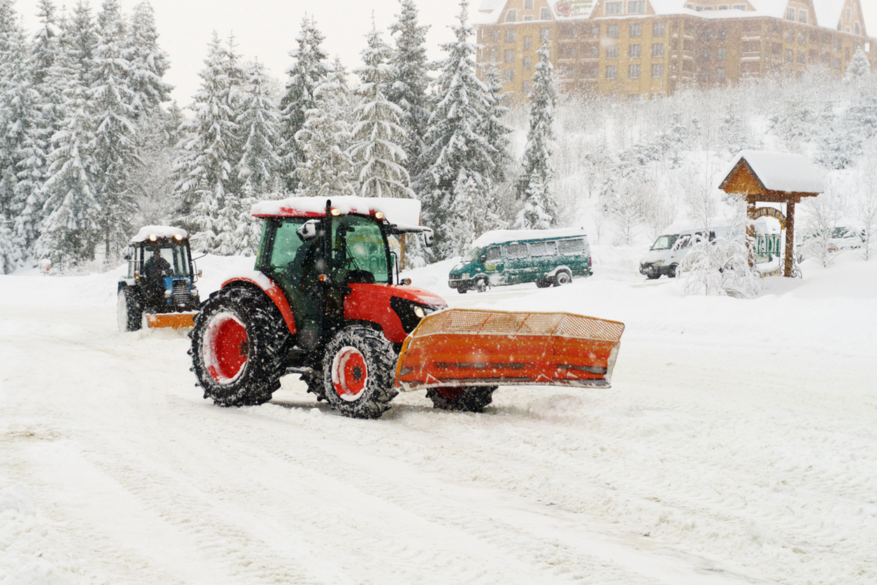 Red and blue tractors clears snow covered road