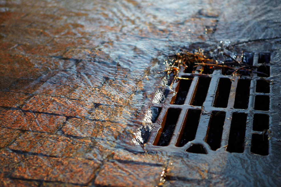 Melted water flows down through the manhole cover on a sunny spring day
