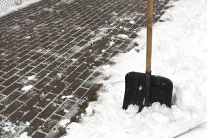 Black plastic snow shovel and pavement. Seasonal background.